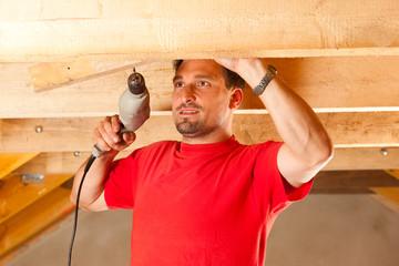 Bauarbeiter oder Heimwerker mit Bohrmaschine