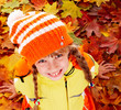 Child in autumn orange leaves.
