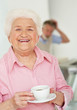 Elderly female holding a cup of tea with blur man in background