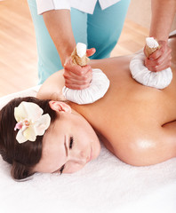 Girl having Thai herb compress massage.