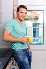 Young man holding a cup of coffee in his kitchen