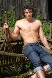 Sexy young male sat on farm machinery