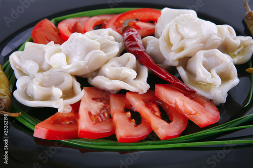 dumplings served with vegetables on black