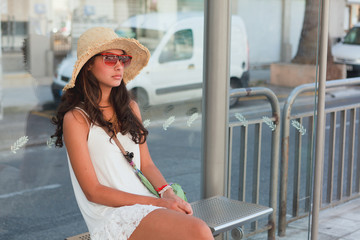 Beautiful young woman waiting for a bus in Nice