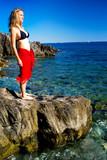 Jeune femme en pareo rouge à la mer poster