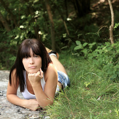 Cute teenage girl laying in the woods