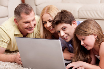 Family lying on carpet in living room with laptop