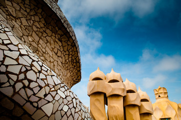 close-up roof top shot of Gaudi's Casa Milà building with blue s