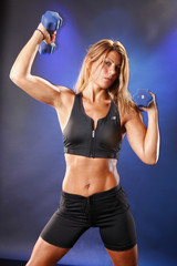 Toned blond working out with dumbells