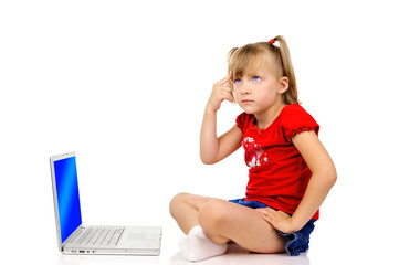 Cute little girl ia thinking with a laptop