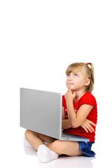 Cute little girl is thinking with a laptop