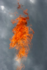 Flame against a grey sky