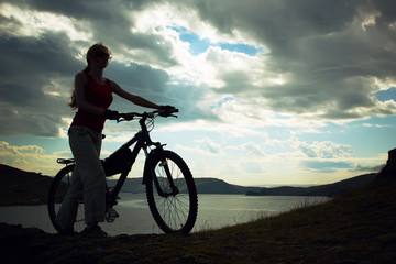 Silhouette of the girl with a bicycle against mountains