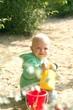 Blond child sittig in sunshine on playground