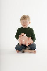 Young Boy Saving Money in a Coin Bank