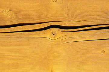 Yellow painted cracked wooden plank close-up