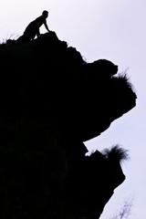 Man on peak of mountain.