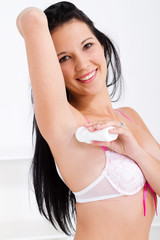 young woman putting deodorant under her arm