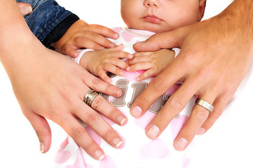 family placing hands on new baby girl with wedding rings visible