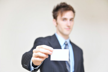 portrait of a young businessman holding blank card