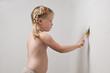 Девочка с косичками трусиках красит стену белой краской