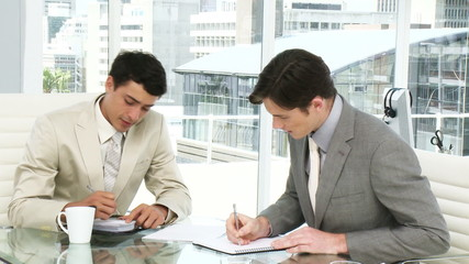 two male executives taking notes during a meeting