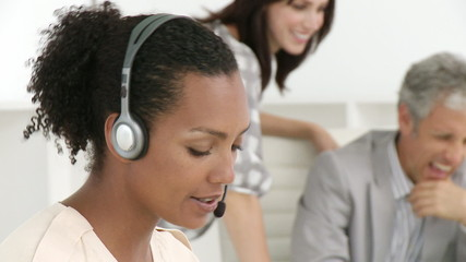 african woman with headset on and he team in background
