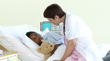 female doctor speaking with a little patient in a room