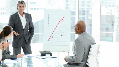 happy man showing graphs to his team