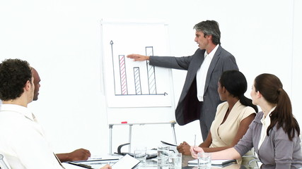 confident manager reporting graphs to his team