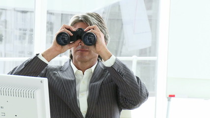 manager looking through spyglasses sitting in his office