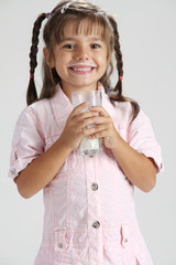 litle cute girl in pink dress holding a glass of milk