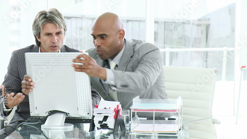 two businessmen fighting with computer