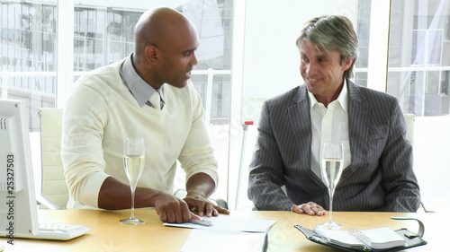 two happy businessmen concluding a contract with champagne