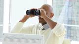 african businessman looking through binoculars in his office