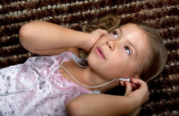 Little girl lying down and listening to music on headphones