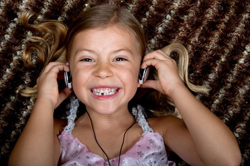 Little girl listening to music on headphones and smiling