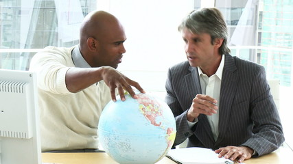 two generations of businessmen looking at a terrestrial globe