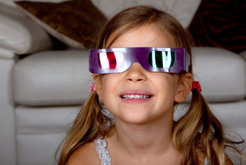 Little girl wearing 3D glasses and watching a film at home