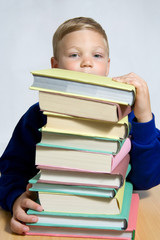 young boy looking out of top of books
