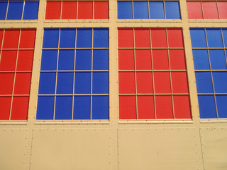 Red and Blue solid colored windows on an old fashion steel wall