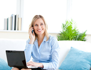 Smiling businesswoman talking on phone and using her laptop sitt