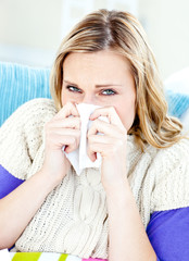 Ill woman using a tissue sitting on a sofa