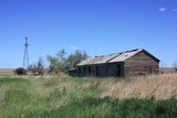 An old ranch with a windmill and an old barn no longer used. poster