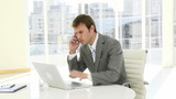 handsome businessman working with laptop and phone in his office