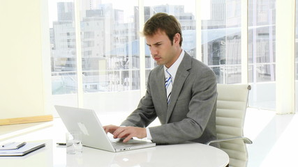 serious businessman working on his laptop in his office