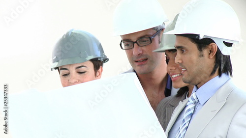 multi-ethnic team of architects watching blueprint