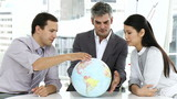 Ambitious businesspeople together around a terrestrial globe