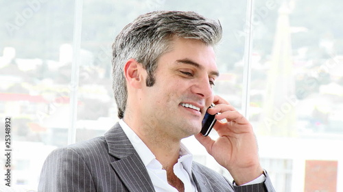 charismatic man on phone sitting in his office