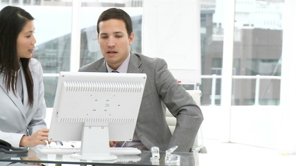 two colleagues working at a computer